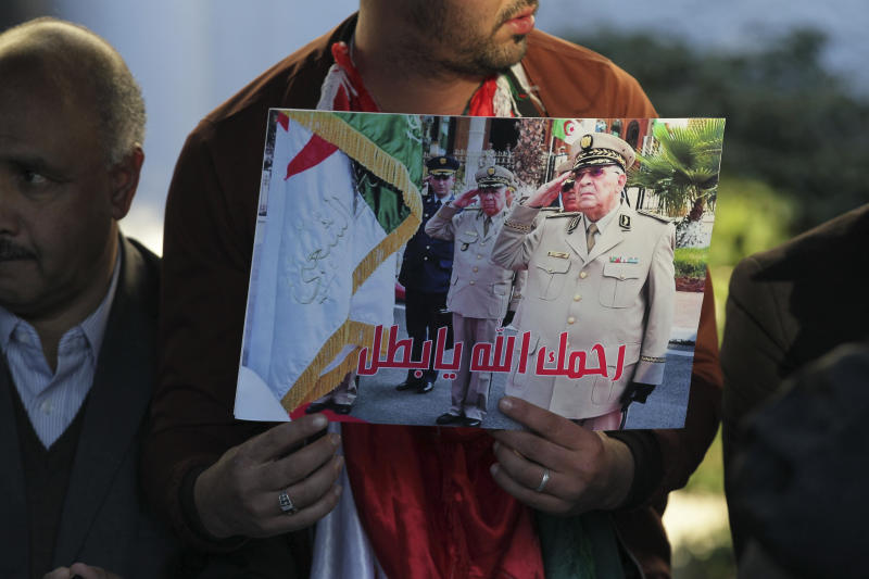 """People attend the funeral of late Algerian military chief Gaid Saleh in Algiers, Algeria, Wednesday, Dec. 25, 2019. Banner in Arabic reads """"May God have his mercy on you, hero"""". Algeria is holding an elaborate military funeral for the general who was the de facto ruler of the gas-rich country amid political turmoil throughout this year. (AP Photo/Fateh Guidoum)"""