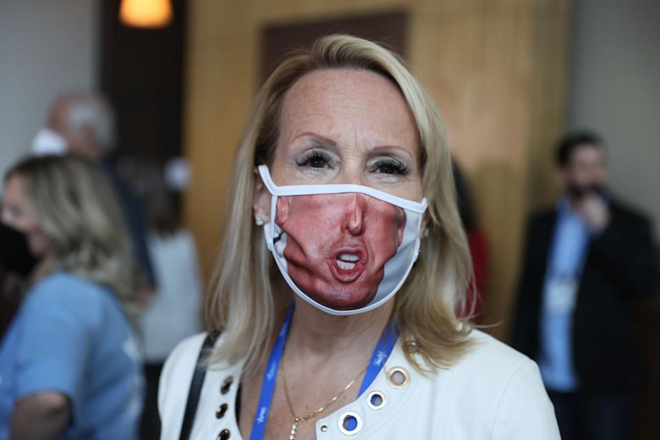 A visitor (who didn't want to provide her name) wears a face mask with a picture of former President Donald Trump on it during the Conservative Political Action Conference on Feb. 26 in Orlando, Florida. (Photo: Photo by Joe Raedle/Getty Images)