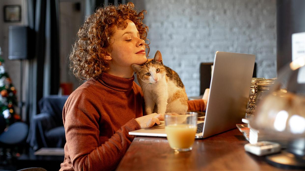 Young woman with cat using laptop.