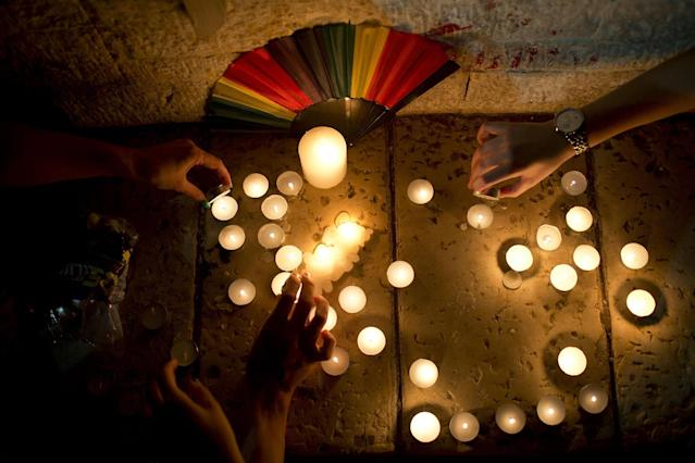 <p>Members LGBT community light candles in solidarity with Florida's shooting attack victims, in Tel Aviv, Israel, June 12, 2016. (AP Photo/Oded Balilty) </p>