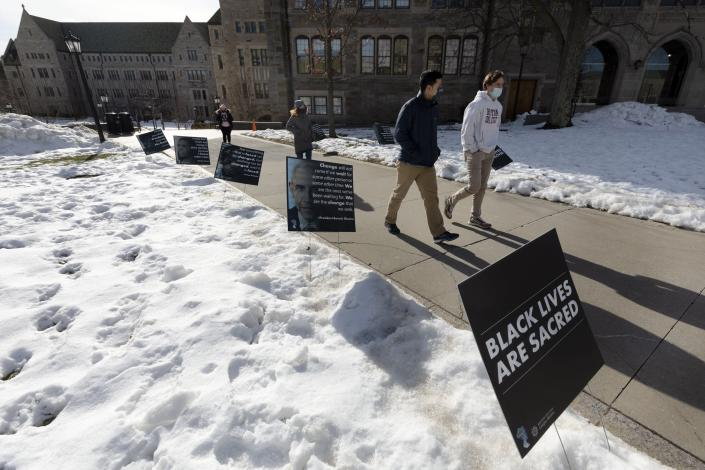 Students walk past Black History Month posters on the Boston College campus, Wednesday, Feb. 17, 2021, in Boston. Harassment by white male students targeting Black and Latina women housed in a Boston College dormitory has revived concerns about racism on campus. (AP Photo/Michael Dwyer)