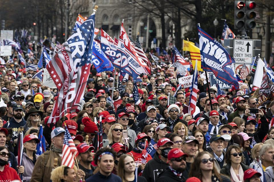 A crowd of Trump supporters wave Trump flags and wear red hats.