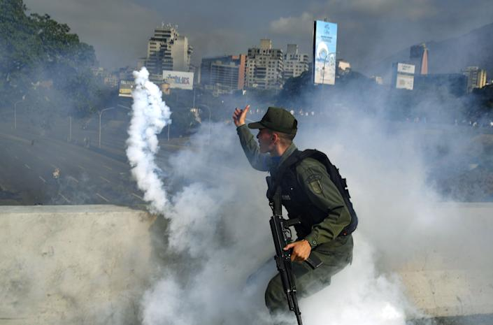 A member of the Bolivarian National Guard supporting Venezuelan opposition leader and self-proclaimed acting president Juan Guaido throws a tear gas canister during a confrontation with guards loyal to President Nicolas Maduro's government in front of La Carlota military base in Caracason April 30, 2019. Yuri Cortez/AFP/Getty Images)