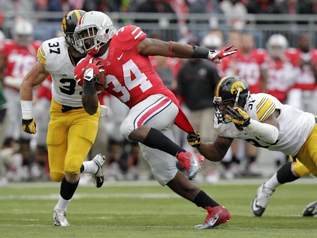 Ohio State running back Carlos Hyde, center, crosses the line of scrimmage between Iowa defenders John Lowdermilk, left, and Anthony Hitchens during the second quarter of an NCAA college football game Saturday, Oct. 19, 2013, in Columbus, Ohio. (AP Photo/Jay LaPrete)