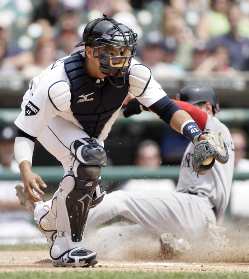 Detroit Tigers catcher Victor Martinez, left, makes the catch but Boston Red Sox's Jacoby Ellsbury beats the ball to home plate to score from third base on a on a sacrifice fly ball by Adrian Gonzalez in the first inning of game one of a baseball double-header Sunday, May 29, 2011 in Detroit. (AP Photo/Duane Burleson)