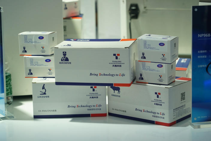 Boxes of reagents from Tianlong, a testing kit company, sits in a display at a trade fair in Nanchang in eastern China's Jiangxi province on Friday, Aug. 21, 2020. Tianlong had made test kits for the coronavirus early in the outbreak but was not designated by the Chinese Center for Disease Control and Prevention, leaving scientists more hesitant to use them in January. (AP Photo/Dake Kang)