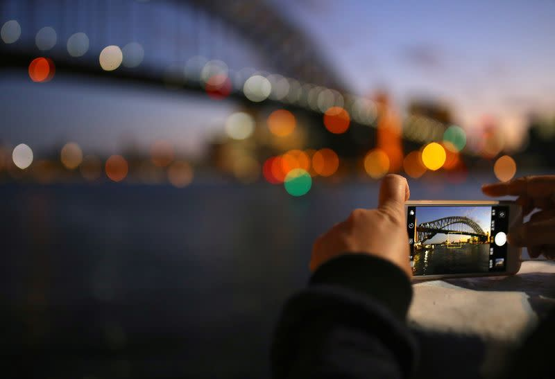 FILE PHOTO: A tourist takes a photograph on their iPhone of the Sydney Harbour Bridge at sunset on a spring day in central Sydney