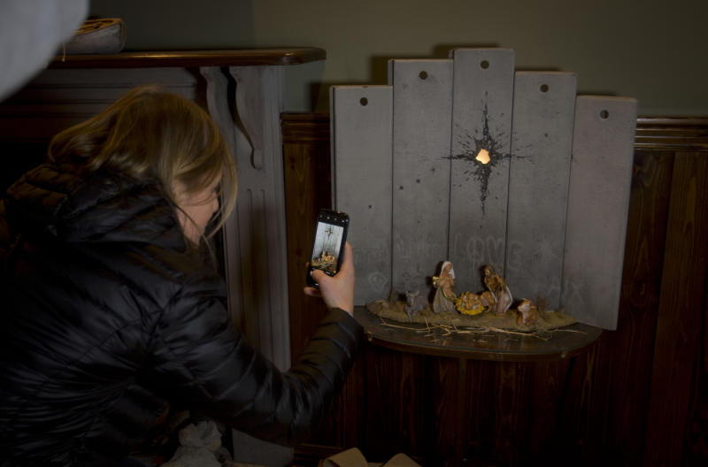 """A Christian visitor takes pictures of a new artwork dubbed """"Scar of Bethlehem"""" by the artist Banksy displayed in The Walled Off Hotel, in the West Bank city of Bethlehem, Sunday, Dec. 22, 2019. (AP Photo/Majdi Mohammed)"""