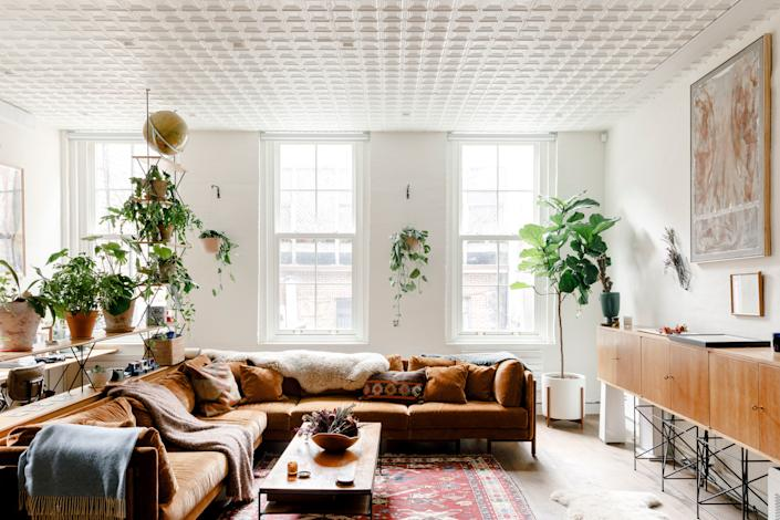 """Harbour searched all over downtown Manhattan to find the ideal New York loft. """"We drew inspiration from the neighborhood vernacular to add back anything that may have once been there in the past,"""" says O'Donnell. """"The goal was to recreate the charm of a vintage NYC loft space, but update it with modern conveniences to suit David's lifestyle."""" Pictured here is the living room, which has vintage touches like a tin ceiling, along with more modern features like a drop-down projector screen."""