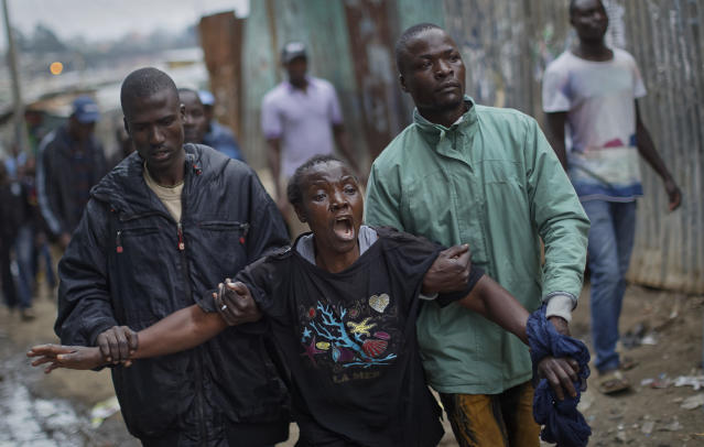 <p>A woman wails and screams at police, near to the body of a man who had been shot in the head and who the crowd claimed had been shot by police, in the Mathare slum of Nairobi, Kenya Wednesday, Aug. 9, 2017. Kenya's election took an ominous turn on Wednesday as violent protests erupted in the capital. (Photo: Ben Curtis/AP) </p>