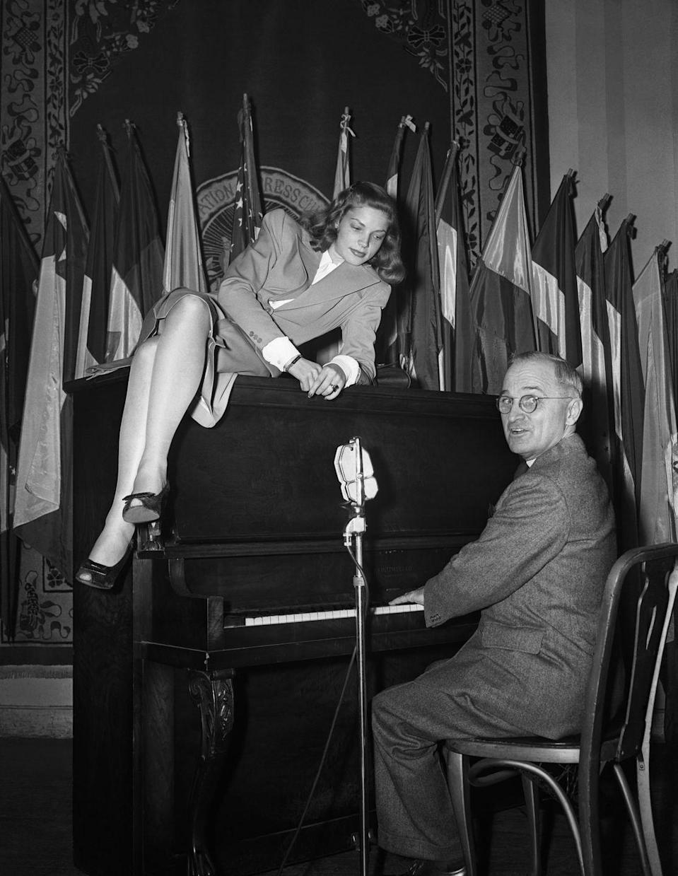 <p>Here, President Truman, who was a pianist, is seen during his time as vice president, tickling the ivories while actress Lauren Bacall poses on top of the piano. </p>