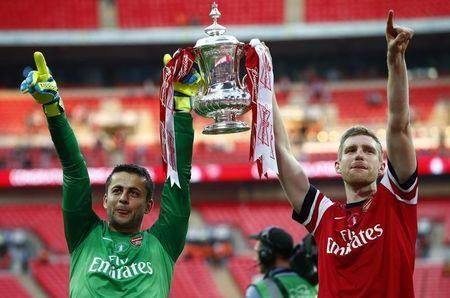 Arsenal's goalkeeper Lukasz Fabianski (L) and Per Mertesacker lift the trophy to celebrate their victory against Hull City in their FA Cup final at Wembley Stadium in London, May 17, 2014. REUTERS/Darren Staples
