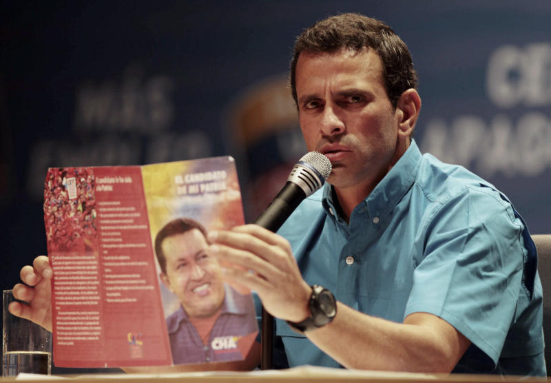Venezuela's opposition presidential candidate Henrique Capriles holds a campaign brochure explaining the platform of President Hugo Chavez during a news conference with foreign correspondents in Caracas, Venezuela, Monday, Oct. 1, 2012. Venezuela's presidential election is scheduled for Oct. 7. (AP Photo/Fernando Llano)