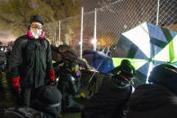 Demonstrators using umbrellas to press against a perimeter security fence and agitate authorities gather during a protest decrying the shooting death of Daunte Wright outside the Brooklyn Center Police Department, Wednesday, April 14, 2021, in Brooklyn Center, Minn. (AP Photo/John Minchillo)