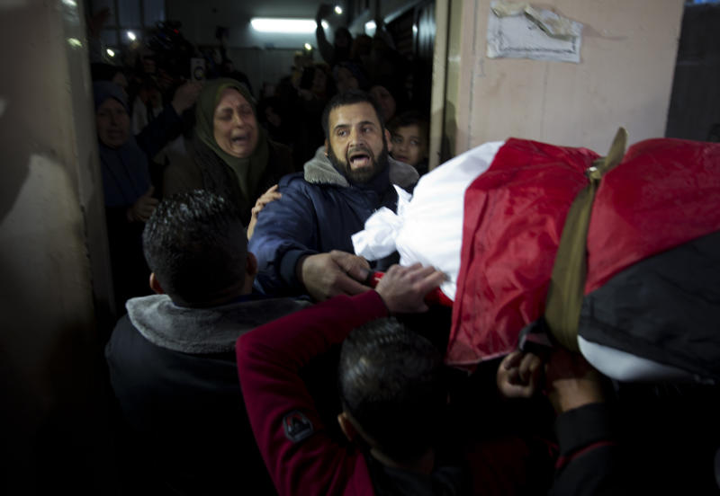 Mourners carry the body of Palestinian woman, Amal al-Taramsi, 43, who was killed by Israeli troops during Friday's protest at the Gaza Strip's border with Israel, into the family home during her funeral in Gaza City, Saturday, Jan. 12, 2019. (AP Photo/ Khalil Hamra)