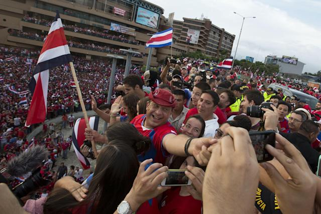 Costa Rica's President Luis Guillermo Solis, center, joins soccer fans celebrating their team's victory over Greece at a Brazil World Cup round of 16 game in San Jose, Costa Rica, Sunday, June 29, 2014. Costa Rica won a penalty shootout 5-3 after the match ended 1-1 following extra time. (AP Photo/Esteban Felix)