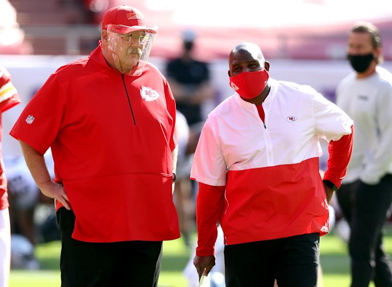 Andy Reid, wearing a face shield, speaks with offensive coordinator Eric Bieniemy, wearing a face mask.