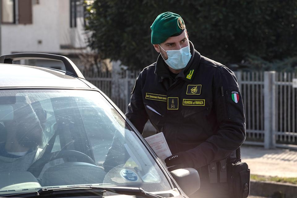 CASALPUSTERLENGO, ITALY - FEBRUARY 24: An Italian Guardia di Finanza (Custom Police) officer, wearing a respiratory mask, stops a vehicle at a road block on February 24, 2020 in Casalpusterlengo, south-west Milan, Italy. Casalpusterlengo is one of the ten small towns placed under lockdown after coronavirus sparked infections throughout the Lombardy region. Italy is the last country to be hit hard by the virus with five dead and more than 224 infected as of today. The spread marks Europe's biggest outbreak, prompting Italian Government to issue draconian safety measures. (Photo by Emanuele Cremaschi/Getty Images)