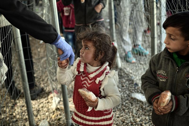 Migrant children get a sandwich at the makeshift camp at the Greek-Macedonian border near the Greek village of Idomeni, on March 2, 2016, where thousands of people are stranded (AFP Photo/Louisa Gouliamaki)