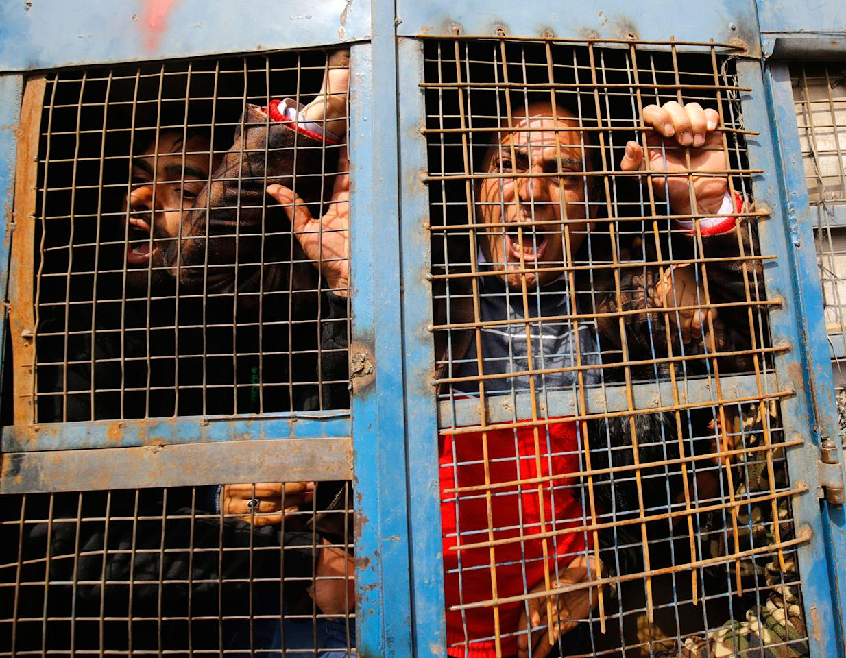 <p>Contractual employees of the National Health Mission shout slogans inside an Indian Police vehicle after they were detained during a protest in Srinagar, the summer capital of Indian Kashmir, 06 March 2017. Indian Police cane charged and arrested half a dozen of employees including doctors and paramedics to disperse them during a protest march when they were demanding regularization of their services. (Farooq Khan/EPA) </p>