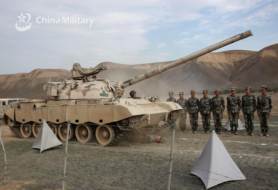 A soldier assigned to an army division under the PLA Xinjiang Military Command lies on the ground as a tank drives over him.