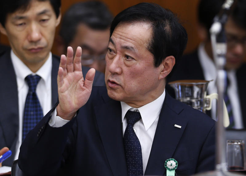 Mizuho Financial Group President Yasuhiro Sato raises a hand before speaking to the Committee on Financial Affairs of the lower house of Parliament in Tokyo Wednesday, Nov. 13, 2013. Japanese banks are pledging more stringent efforts to prevent dealings with organized crime after an investigation into such lending at Mizuho prompted disclosures of wider problems. Sato forfeited six months pay, and the chairman of Mihuzo's banking business resigned. Asked if that was penalty enough, Sato acknowledged some people were calling for harsher penalties, but noted that his bank was not the only lender to have been caught extending mob-linked loans. (AP Photo/Shuji Kajiyama)