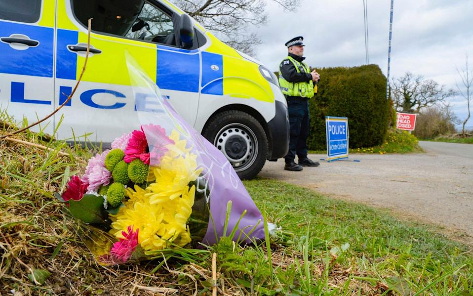 Flowers left at the entrance to the driveway which leads to Sir Richard's house -  Graham Hunt/BNPS