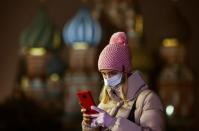 A woman uses her mobile phone before the opening of an outdoor skating rink in the Red Square in Moscow