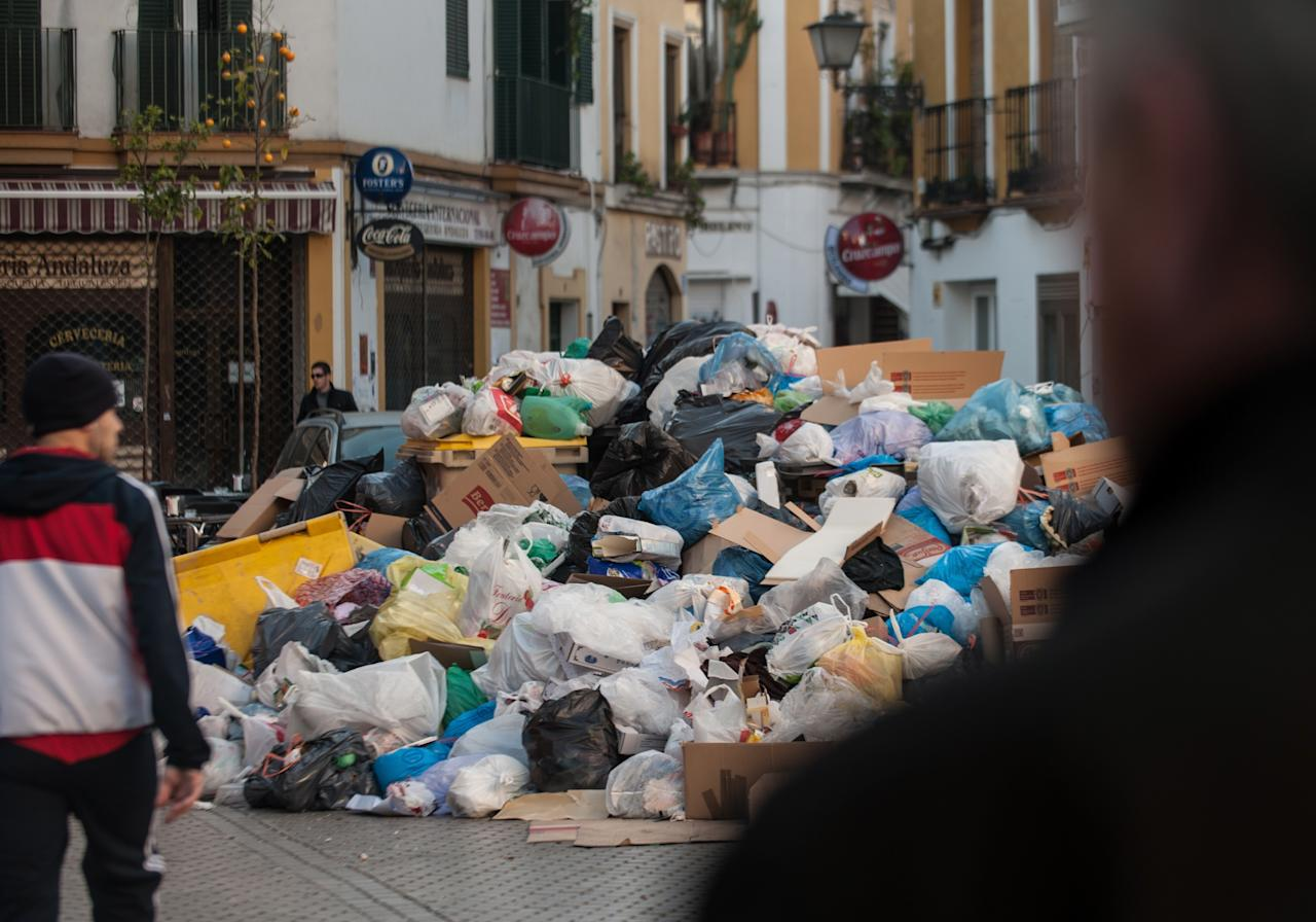 SEVILLE, SPAIN - FEBRUARY 05:  Pedestrians pass a pile of garbage during the ninth day of the Seville waste disposal strike on February 5, 2013 in Seville, Spain. Workers are striking over demands they take a 5% pay cut and extend their working week to 37.5 hours.  (Photo by Denis Doyle/Getty Images)