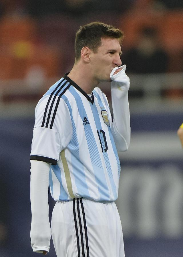 Argentina's Lionel Messi wipes his mouth after appearing to vomit on the pitch during an international friendly soccer game against Romania on the National Arena stadium in Bucharest, Romania, Wednesday, March 5, 2014. (AP Photo)