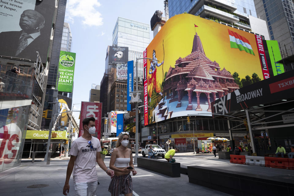 People pass by the imagery of the Hindu deity Ram and 3-D portraits of the proposed Hindu temple are displayed on a digital billboard in Time Square, New York, Wednesday, Aug. 5, 2020, to celebrate the groundbreaking ceremony of a temple dedicated to the Hindu god Ram by Indian Prime Minister Narendra Modi in Ayodhya, in New Delhi, India. Hindus rejoiced as Modi broke ground on a long-awaited temple of their most revered god, Ram, at the site of a demolished 16th century mosque. (AP Photo/Mark Lennihan)