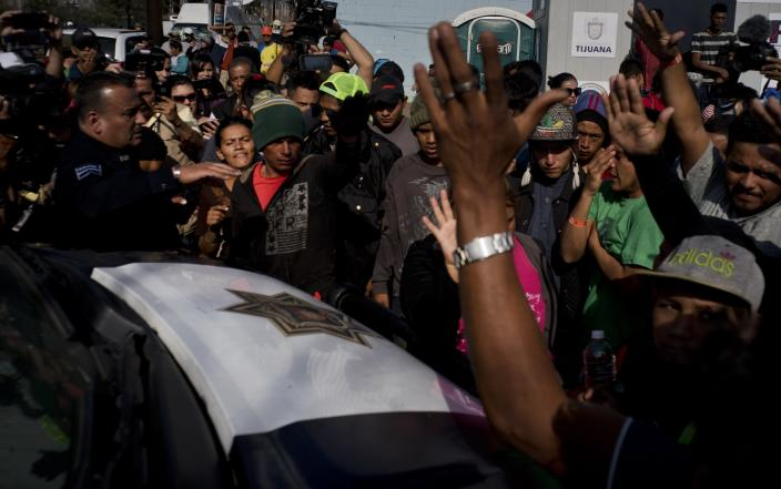 Immigrants argue with the police after they detained two men for smoking marijuana, in Tijuana, Mexico, Wednesday, Nov. 21, 2018. Migrants camped in Tijuana after traveling in a caravan reach the US are weighing their options after a US court blocked President Donald Trump's asylum for illegal border crossers. (AP Photo / Ramon Espinosa)