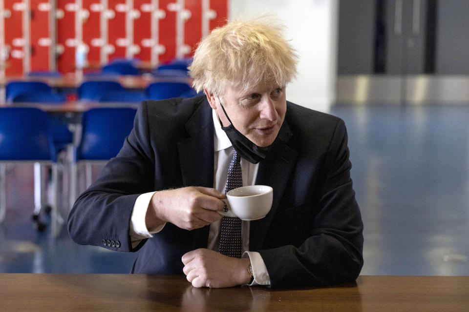 Britain's Prime Minister Boris Johnson drinks a coffee while speaking with pupils after taking part in a science lesson, during a visit to King Solomon Academy in London, Thursday April 29, 2021.  (Dan Kitwood/Pool via AP)