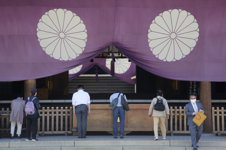 Worshippers bow while visiting Yasukuni Shrine in Tokyo, Wednesday, April 21, 2021, the first day of the annual Spring Rites, the Shinto shrine's biannual festival honoring the war dead. (AP Photo/Koji Sasahara)
