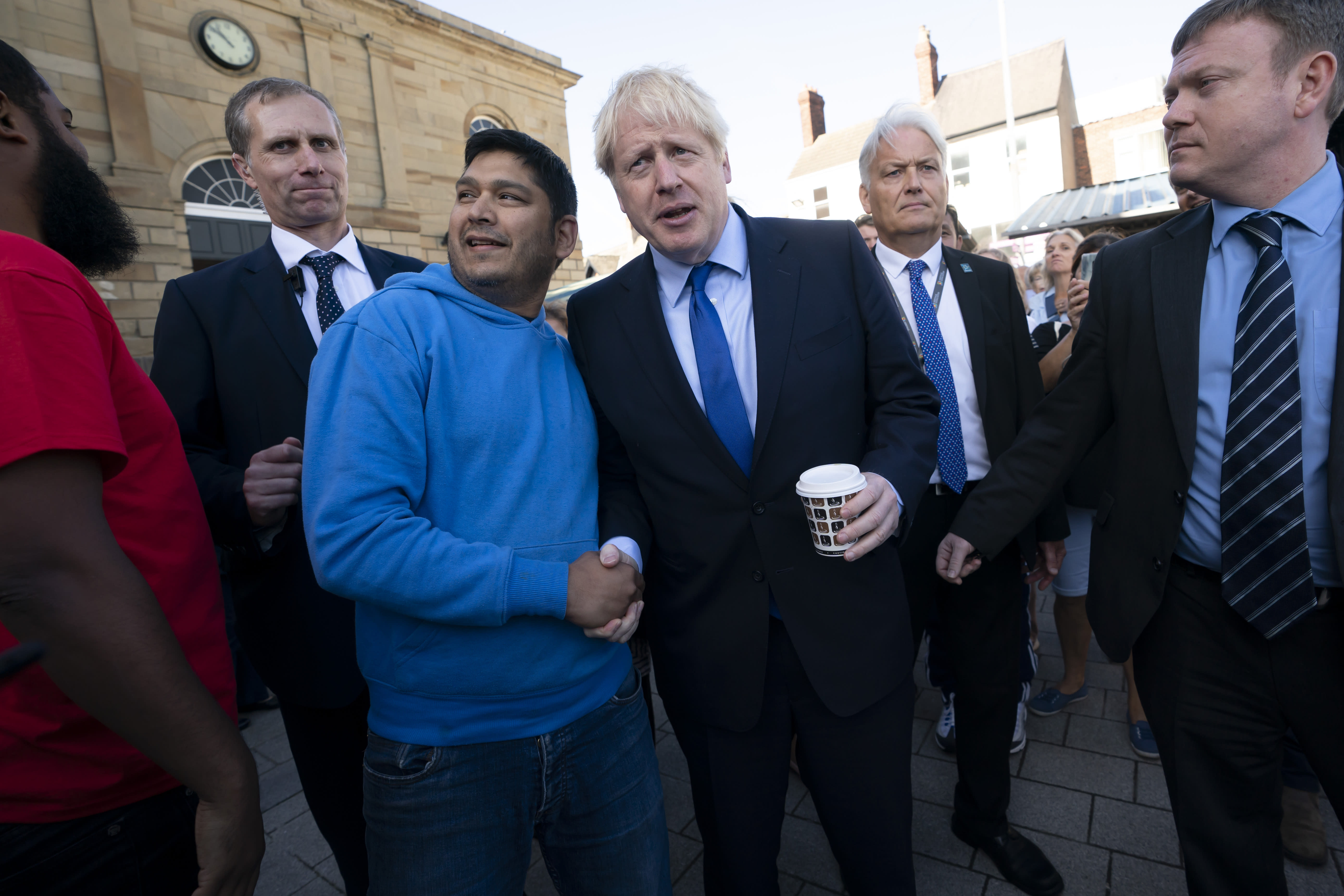 Prime Minister Boris Johnson shakes hands with a member of the public during his visit Doncaster Market, in Doncaster.