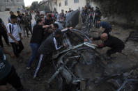 Palestinians gather around a car after it was hit by an Israeli airstrike, in Gaza City, Saturday, May 15, 2021. (AP Photo/Mohammed Ali)