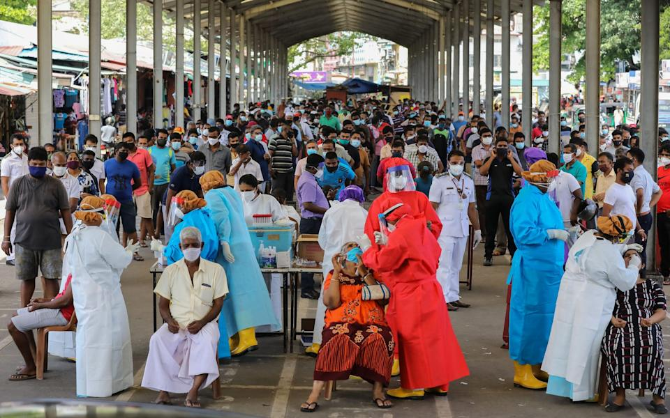 People wait as health workers carry out Covid-19 swab tests at a bus terminal in Colombo - CHAMILA KARUNARATHNE/EPA-EFE/Shutterstock