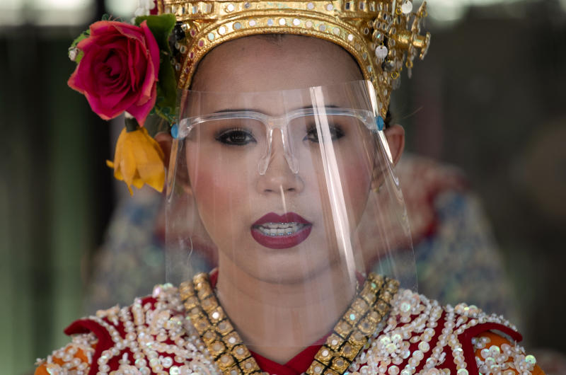 A Thai classical dancer wearing face shield to help curb the spread of the coronavirus performs at the Erawan Shrine in Bangkok, Thailand, Thursday, May 28, 2020. Thai government continues to ease restrictions related to running business in capital Bangkok that were imposed weeks ago to combat the spread of COVID-19. (AP Photo/Sakchai Lalit)