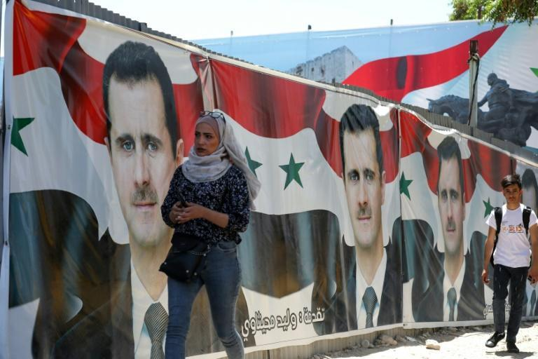 Syrians walk next to campaign billboards depicting President Bashar al-Assad in the capital Damascus, ahead of polls he is widely expected to win