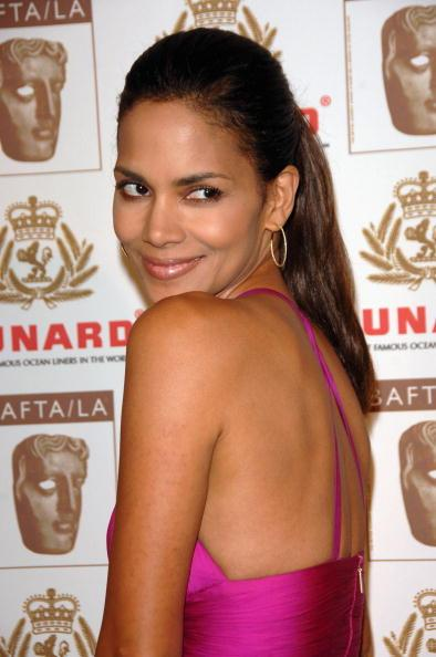 <p>Halle Berry uses a ponytail to show off the back of her dress.</p>