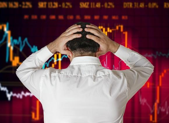 An investors holds his head in despair in front of a financial chart.