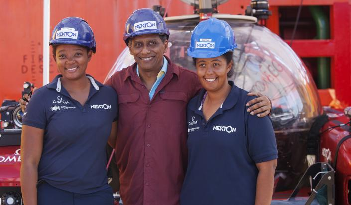 In this Saturday, April 13, 2019, photo, Seychelles President Danny Faure, center, smiles for a photograph with two young Seychellois scientists on board the Ocean Zephyr, off the coast of Desroches, in the outer islands of Seychelles. President Faure was visiting a British-led science expedition exploring the depths of the Indian Ocean where scientists documented changes taking place beneath the waves that could affect billions of people in the surrounding region over the coming decades. (AP Photo/Steve Barker)