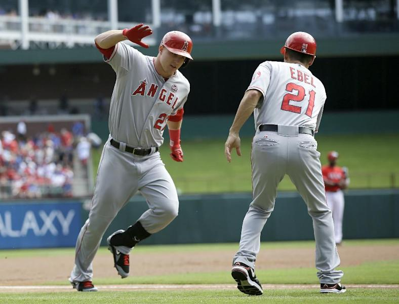 Los Angeles Angels' Mike Trout (27) is congratulated by third base coach Dino Ebel (21) following his solo home run hit off Texas Rangers starting pitcher Yu Darvish in the first inning of a baseball game on Sunday, Sept. 29, 2013, in Arlington, Texas. (AP Photo/Tony Gutierrez)