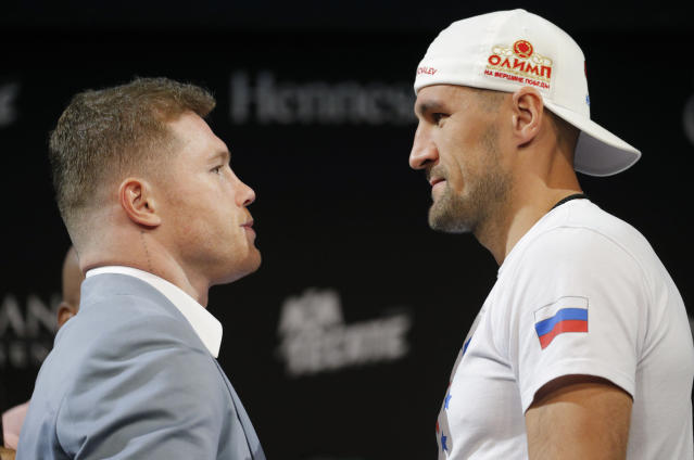 Sergey Kovalev, right, and Canelo Alvarez pose for photographers during a news conference Wednesday, Oct. 30, 2019, in Las Vegas. The two are scheduled to fight in a WBO light heavyweight title bout Saturday in Las Vegas. (AP Photo/John Locher)