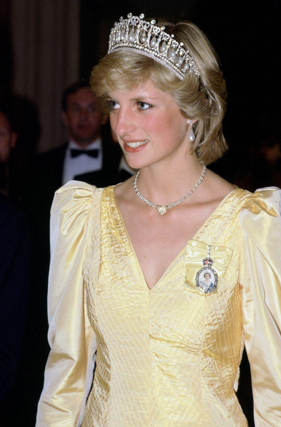 <p>A vision in yellow, the princess brought back the Cambridge Lover's Knot tiara, showing off the headpiece's drop pearls and diamonds. Around Diana's neck is a heart-shaped diamond necklace, a push present from Prince Charles to celebrate Prince William's birth. <br></p>