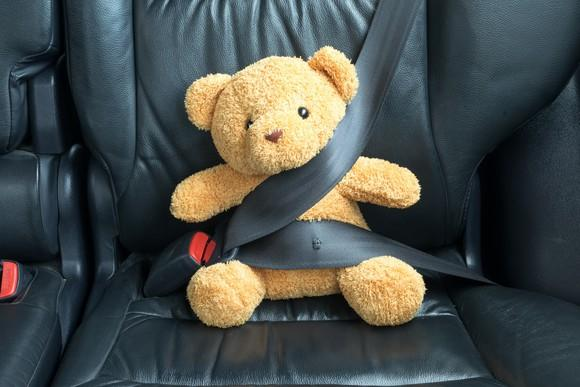 Stuffed bear in carseat with seatbelt around it.