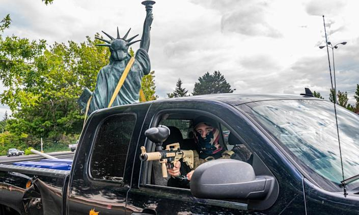 A member of the far-right group the Proud Boys aims a paintball gun while leaving a demonstration with a Statue of Liberty replica in the bed of the truck.
