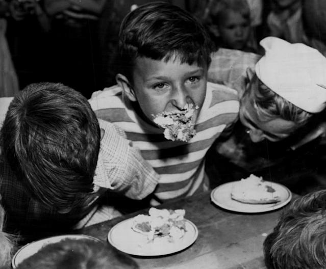 <p>His Mouth Full, his face smeared, one contestant comes up for air while his opponents dig deeper into their pie in the course of the pie-eating contest at Central City's July Fourth celebration in Colo., 1947. The afternoon's events, in addition to pie eating, included three-legged races, a greased pig, and other traditional contests. (Photo: Denver Post via Getty Images) </p>
