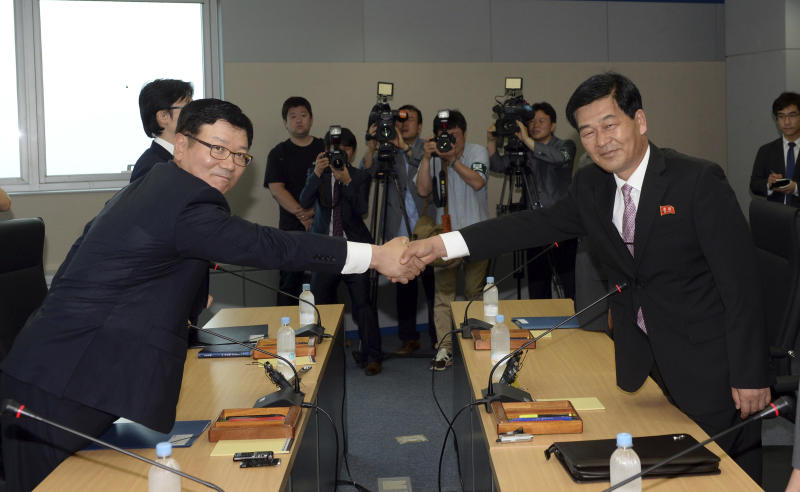 Suh Ho, the head of South Korea's working-level delegation, left, shakes hands with his North Korean counterpart Park Chol Su, right, before their meeting at Kaesong Industrial District Management Committee in Kaesong, North Korea, Wednesday, July 10, 2013. They met to discuss how to restart a shuttered factory complex that had been run by both Koreas until its shutdown in April. (AP Photo/Korea Pool vis Yonhap) KOREA OUT