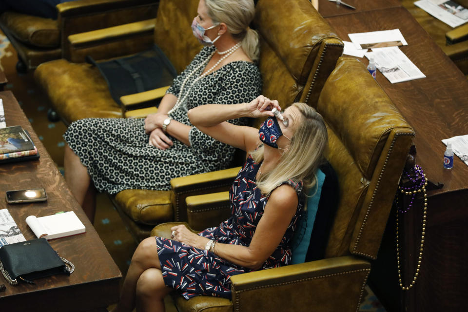 Rep. Dana McLean, R-Columbus, takes advantage of a brief recess at the Legislature to use some eyedrops while staying face masked and maintaining some social distance from row mate Rep. Jill Ford, R-Madison, Monday, Aug. 10, 2020, at the Capitol in Jackson, Miss. The legislators were in Jackson to finish the final parts of a state spending plan for the budget year that began July 1, and to override a number of passed legislation vetoes by Gov. Tate Reeves. (AP Photo/Rogelio V. Solis)